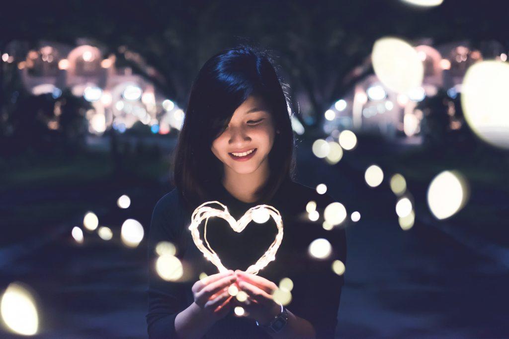Une jeune femme tenant un coeur en guirlande lumineuse dans ses mains