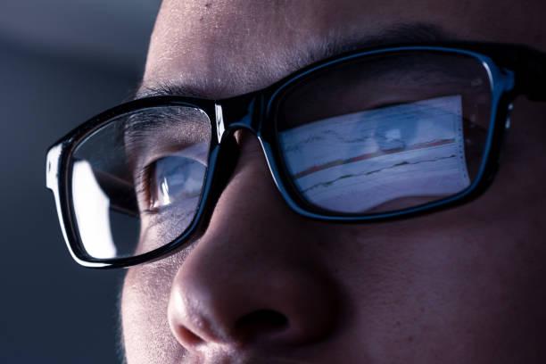 Jeune homme qui porte des lunettes pour travailler sur son ordinateur