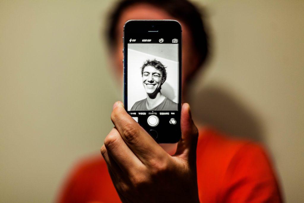 Un jeune homme preannt un selfie sur un iphone noir