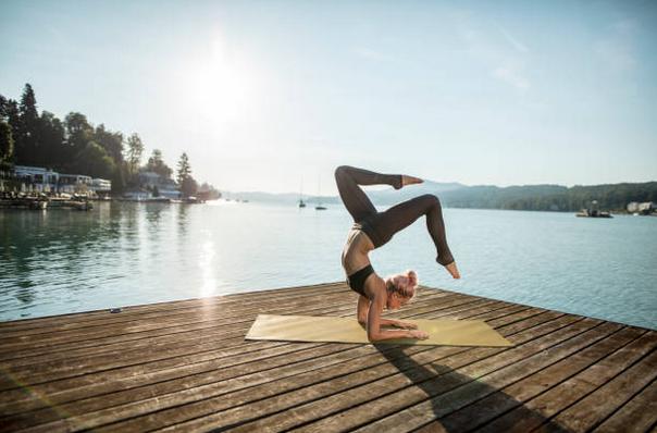 Femme qui réalise une posture complexe de yoga sur le ponton d'un lac