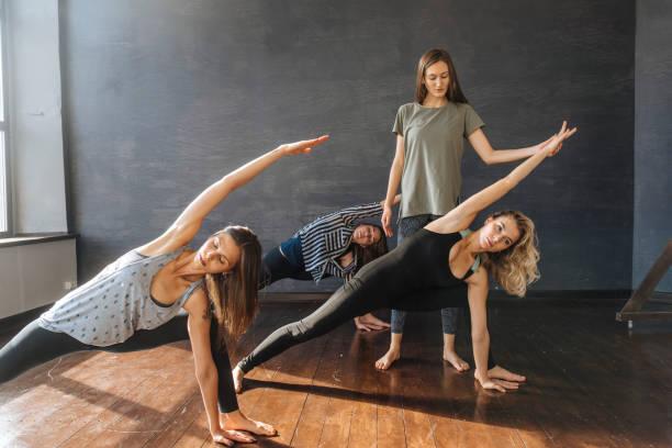 Trois femmes qui réalisent une posture de yoga et une professeur qui les conseille