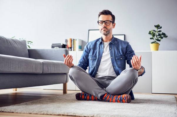 Homme assis en tailleur sur le tapis de son salon, les yeux fermés et l'air détendu