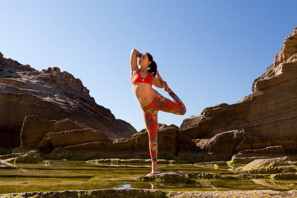 Femme qui réalise une posture de hatha yoga au milieu de roches naturelles