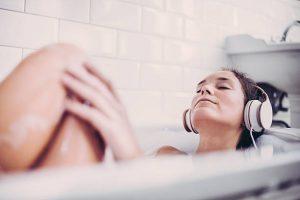 Femme profitant des bienfaits du son d'avoine dans son bain les yeux fermés en écoutant de la musique