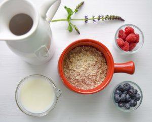 Mug rouge rempli de son d'avoine vu de haut avec fruits et lait à côté