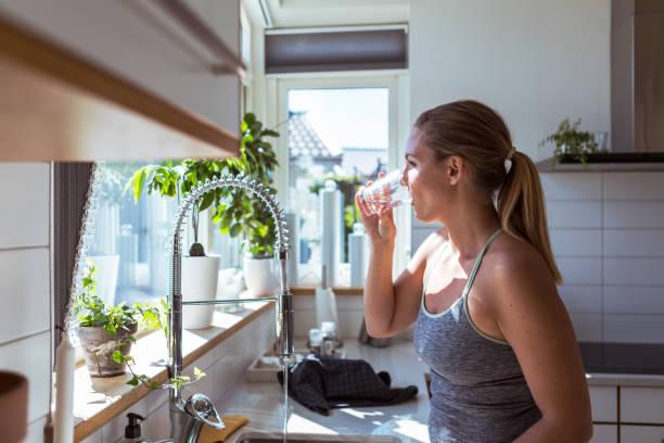 Femme qui boit un verre d'eau dans sa cuisine