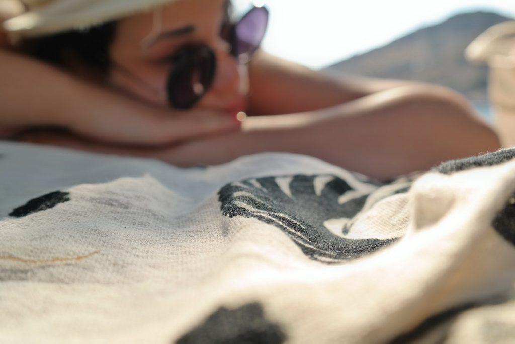 Jeune femme qui bronze sur sa serviette de plage