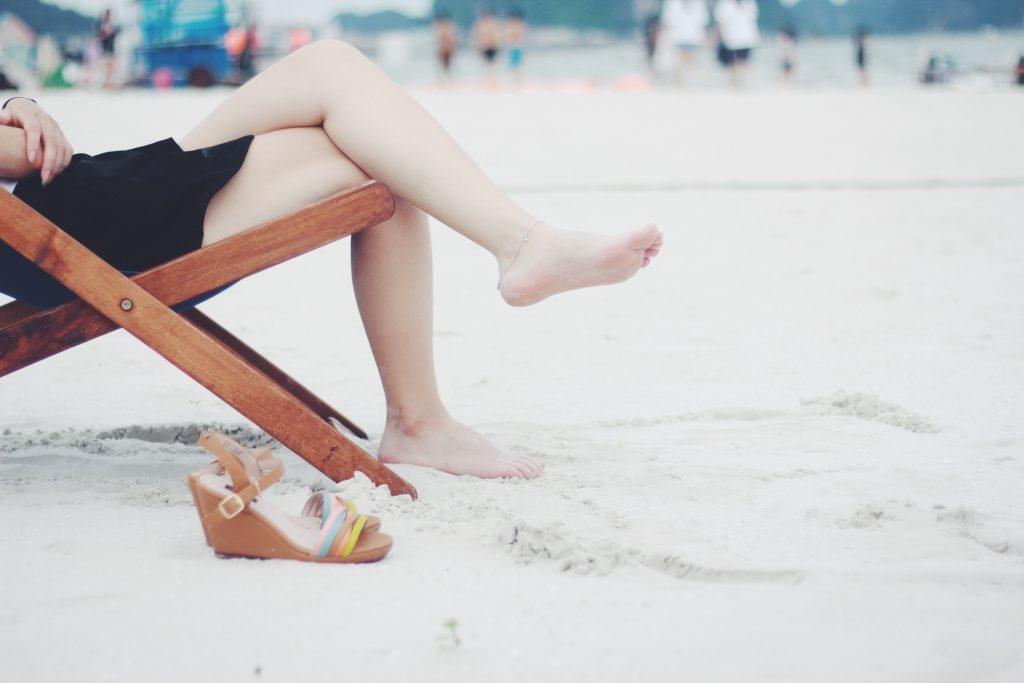 Jambes d'une femme allongée dans un transat à la mer