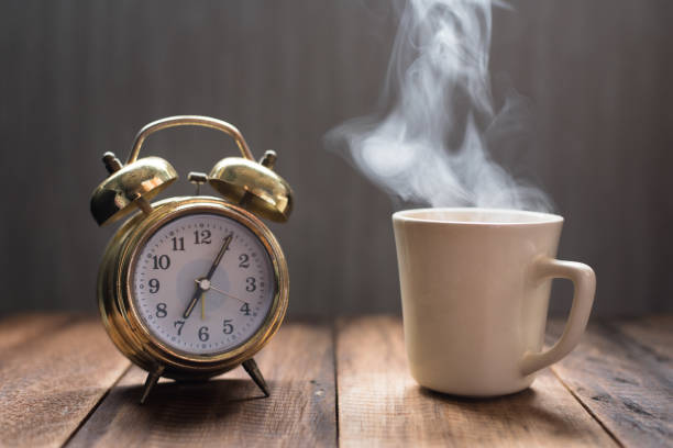 Tasse bouillante et ancien réveil sur une table en bois