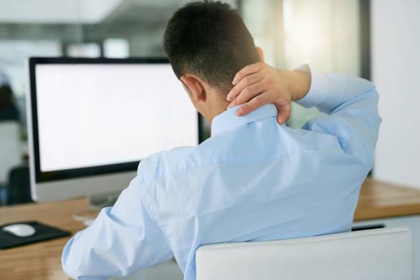 Jeune homme au travail avec douleur aux cervicales à cause de sa position assise au bureau