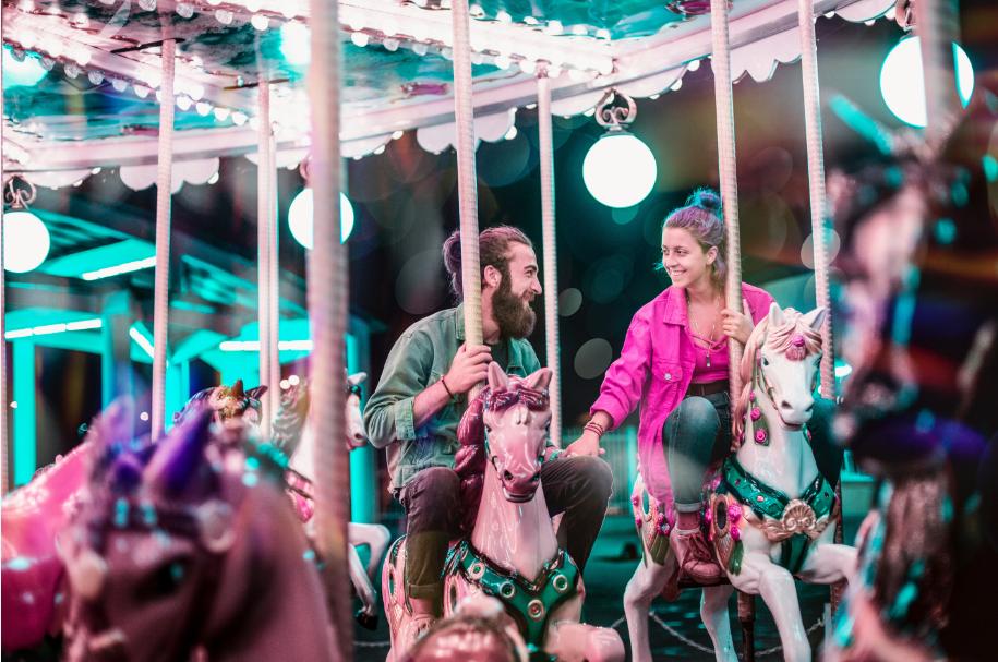 Couple qui rie sur les chevaux de bois d'un manège