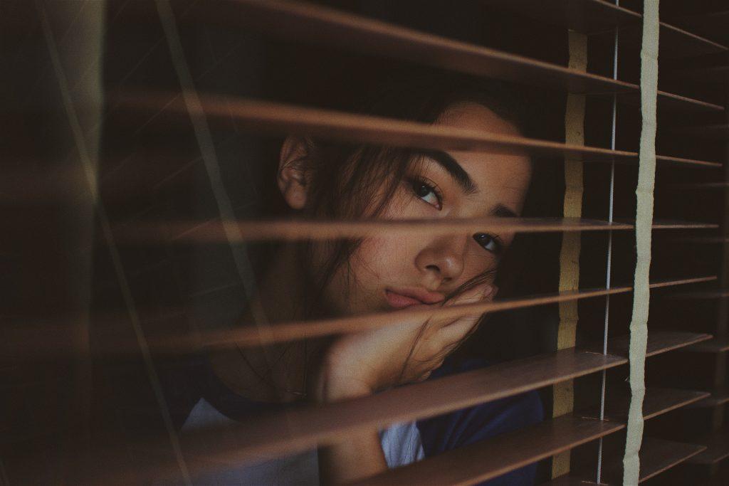 Jeune fille qui regarde par la fenêtre, une main dans son visage en signe d'ennui