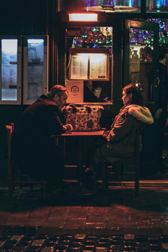 Un homme et une femme qui se font face à la table d'une terrasse