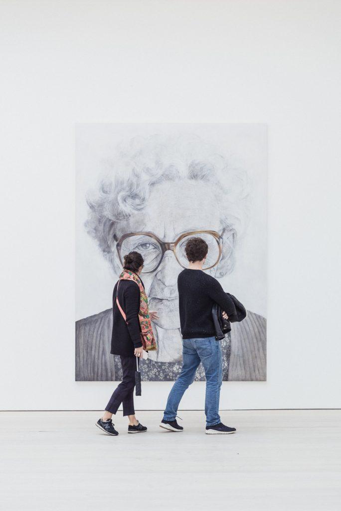 Un couple qui marche devant un grand tableau, dans un musée