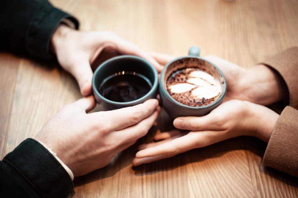 Gros plan sur les mains de deux personnes qui tiennent une tasse de café au centre de la table