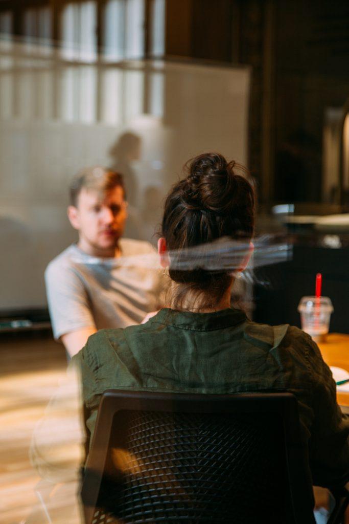 Femme de dos qui partage la table d'un café avec un homme