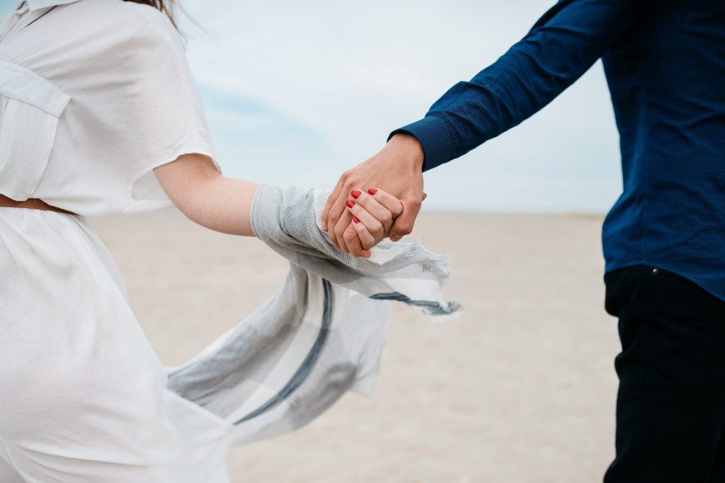 Un couple qui se tient la main en marchant sur la plage