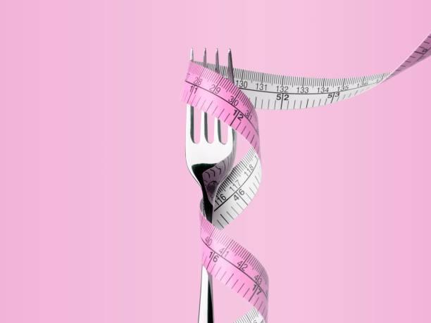 Fourchette avec un ruban de mesure sur fond rose